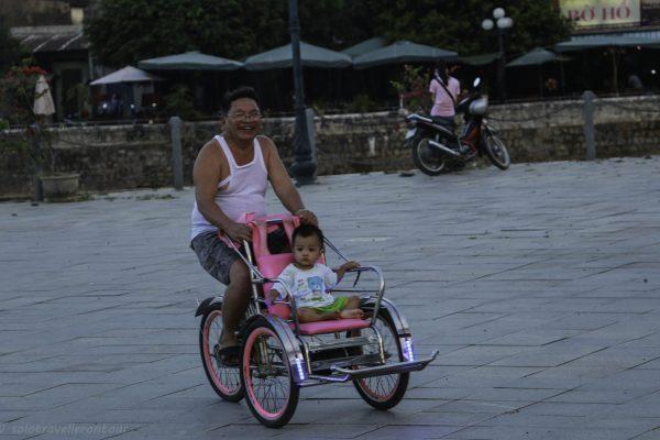 A father enjoying the cyclo ride more than his son