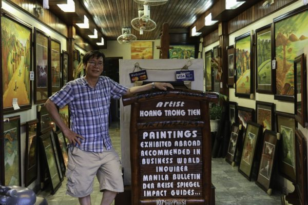 Tien the artist with some of his painting