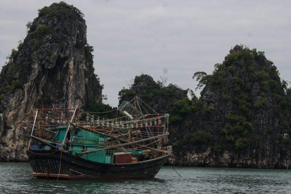 Fishing boat next to a limestone karst