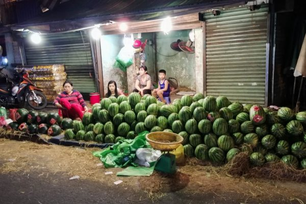 The locals carefully build up the stack of melons